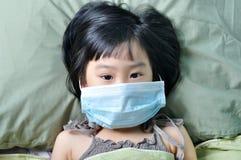 Muchacha asiática de la enfermedad de la gripe pequeña en máscara de la atención sanitaria de la medicina Foto de archivo libre de regalías