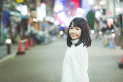 Muchacha asiática de la muchacha que camina en la calle de la ciudad de la noche Imágenes de archivo libres de regalías