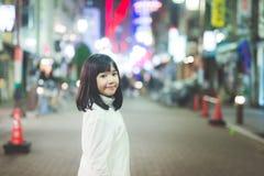 Muchacha asiática de la muchacha que camina en la calle de la ciudad de la noche Imagen de archivo libre de regalías