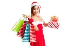 Muchacha asiática de la Navidad con la ropa de Papá Noel, la caja de regalo y compras Imagen de archivo