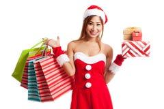Muchacha asiática de la Navidad con la ropa de Papá Noel, la caja de regalo y compras Foto de archivo