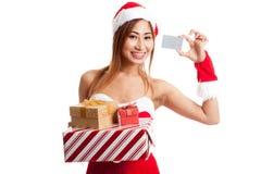 Muchacha asiática de la Navidad con la ropa de Papá Noel, la caja de regalo y la tarjeta Imagenes de archivo