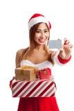Muchacha asiática de la Navidad con la ropa de Papá Noel, la caja de regalo y la tarjeta Imagen de archivo