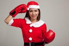 Muchacha asiática de la Navidad con la ropa de Santa Claus y el guante de boxeo Fotografía de archivo libre de regalías