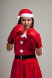Muchacha asiática de la Navidad con la ropa de Santa Claus y el guante de boxeo Imagen de archivo
