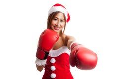 Muchacha asiática de la Navidad con la ropa de Santa Claus y el guante de boxeo Foto de archivo