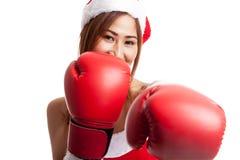 Muchacha asiática de la Navidad con la ropa de Santa Claus y el guante de boxeo Fotografía de archivo