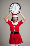 Muchacha asiática de la Navidad en la ropa y el reloj de Santa Claus en el midnigh imagenes de archivo