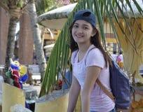 Muchacha asiática de Millenial que lleva un casquillo y una mochila con el backgound del árbol de la hoja del coco y de coco Fotografía de archivo