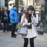 Muchacha asiática de moda en vidrios con un bolso gris que habla en el teléfono Fotografía de archivo