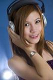 Muchacha asiática de pelo largo que escucha la música Imagenes de archivo