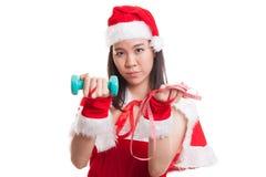 Muchacha asiática de Santa Claus de la Navidad con la cinta métrica y el dumbbel Imagen de archivo libre de regalías