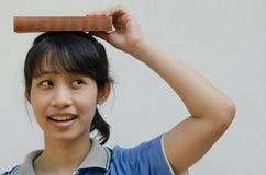 Muchacha asiática del adolescente que piensa cuando ella que pone un libro en la cabeza Foto de archivo