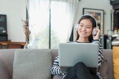 Muchacha asiática del adolescente que usa el ordenador portátil y la música que escucha encendido Imagenes de archivo