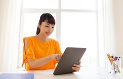 Muchacha asiática del estudiante con PC de la tableta que aprende en casa Fotografía de archivo