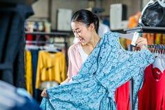 Muchacha asiática del inconformista que elige la ropa en alameda de compras Foto de archivo
