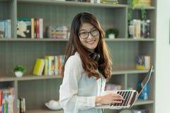 Muchacha asiática del negocio que usa un ordenador portátil en biblioteca en la oficina, persona foto de archivo libre de regalías
