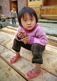 Muchacha asiática del niño 4 años, sosteniendo la galleta, en campo. Fotos de archivo