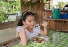 Muchacha asiática del niño que come el cerdo de la albahaca en Tailandia fotografía de archivo libre de regalías