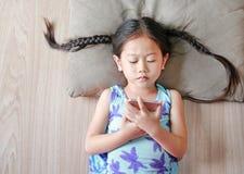 Muchacha asiática del niño que mira el smartphone que miente en piso de madera Visión superior foto de archivo libre de regalías
