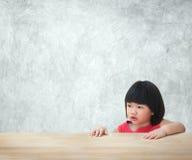 Muchacha asiática del niño que se sienta detrás de la tabla vacía con el fondo del muro de cemento Foto de archivo libre de regalías
