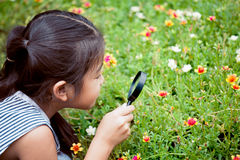 Muchacha asiática del pequeño niño que mira a través de una lupa Imágenes de archivo libres de regalías
