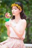 Muchacha asiática del retrato con la flor del juguete Fotos de archivo