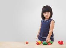 Muchacha asiática divertida que juega con el juguete de cocinar de madera, pequeño cocinero del niño que prepara la comida en la  Imágenes de archivo libres de regalías