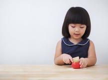 Muchacha asiática divertida que juega con el juguete de cocinar de madera, pequeño cocinero del niño que prepara la comida en la  Imagen de archivo libre de regalías