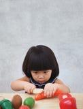 Muchacha asiática divertida que juega con el juguete de cocinar de madera, pequeño cocinero del niño que prepara la comida en la  Fotografía de archivo libre de regalías