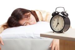 Muchacha asiática durmiente con el despertador Fotografía de archivo libre de regalías