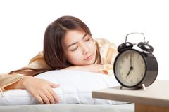 Muchacha asiática durmiente con el despertador Imagenes de archivo