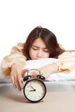 Muchacha asiática durmiente con el despertador Fotos de archivo libres de regalías