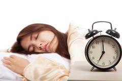 Muchacha asiática durmiente con el despertador Foto de archivo libre de regalías