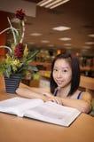 Muchacha asiática en biblioteca fotos de archivo