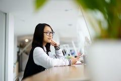 Muchacha asiática en coworking después de lecciones en la escuela usando la conexión a internet inalámbrica y el smartphone Foto de archivo