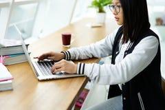 Muchacha asiática en coworking usando la conexión inalámbrica a Internet en campus de la universidad Fotos de archivo