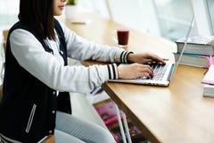 Muchacha asiática en coworking usando la conexión a internet inalámbrica en campus Imagen de archivo libre de regalías