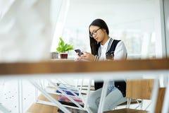 Muchacha asiática en coworking usando la conexión a internet inalámbrica y smartphone en cafetería moderna Imagen de archivo
