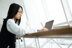 Muchacha asiática en coworking y conexión inalámbrica a Internet mientras que se sienta en sala de clase Imágenes de archivo libres de regalías