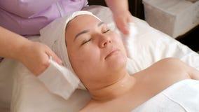 Muchacha asiática en el procedimiento en el salón de belleza Masaje, rejuvenecimiento y limpiamiento facial Las manos de las muje almacen de video