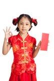 Muchacha asiática en la AUTORIZACIÓN china de la demostración del vestido del cheongsam con el sobre rojo Fotografía de archivo libre de regalías
