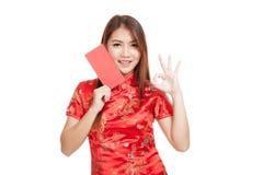 Muchacha asiática en la AUTORIZACIÓN china de la demostración del vestido del cheongsam con el sobre rojo Fotos de archivo libres de regalías