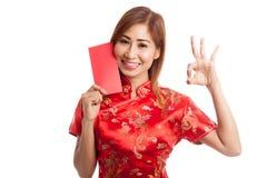 Muchacha asiática en la AUTORIZACIÓN china de la demostración del vestido del cheongsam con el sobre rojo Imagen de archivo