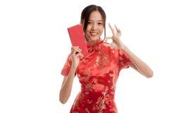 Muchacha asiática en la AUTORIZACIÓN china de la demostración del vestido del cheongsam con el sobre rojo Imágenes de archivo libres de regalías