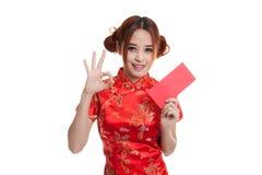 Muchacha asiática en la AUTORIZACIÓN china de la demostración del vestido del cheongsam con el sobre rojo Imagen de archivo libre de regalías
