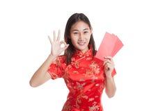 Muchacha asiática en la AUTORIZACIÓN china de la demostración del vestido del cheongsam con el sobre rojo Fotos de archivo