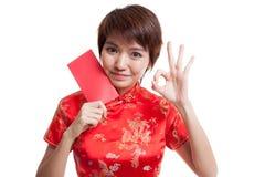Muchacha asiática en la AUTORIZACIÓN china de la demostración del vestido del cheongsam con el sobre rojo Fotografía de archivo