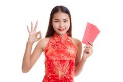 Muchacha asiática en la AUTORIZACIÓN china de la demostración del vestido del cheongsam con el sobre rojo Foto de archivo