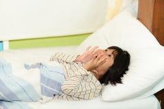 Muchacha asiática en la cama en casa que oculta debajo de la manta Imágenes de archivo libres de regalías